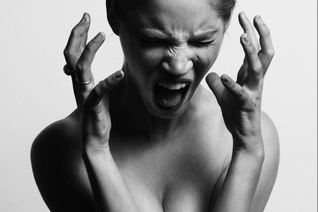 grayscale photography of woman opening her mouth while hanging her hands near her face